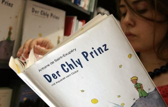 """BERN, SWITZERLAND: TO GO WITH AFP STORY BY PAMELA TAYLOR A teen reads 24 May 2006 a Bernerdeutsch editions of """"Le Petit Prince"""" in a bookshop in Bern. To mark this year's 60th anniversary of the European publication of Antoine St. Exupery's """"Le Petit Prince"""", a translation has appeared in Bernerdeutsch, the Swiss German dialect from the area of Bern, under the title """"Der Chyl Prinz"""". Historically standard German, or Hochdeutsch, has been the official written language for 64 percent of the Swiss population, followed by French (19 percent), Italian (8 percent) and a Latin dialect known as Romansch. AFP PHOTO FABRICE COFFRINI (Photo credit should read FABRICE COFFRINI/AFP via Getty Images)"""