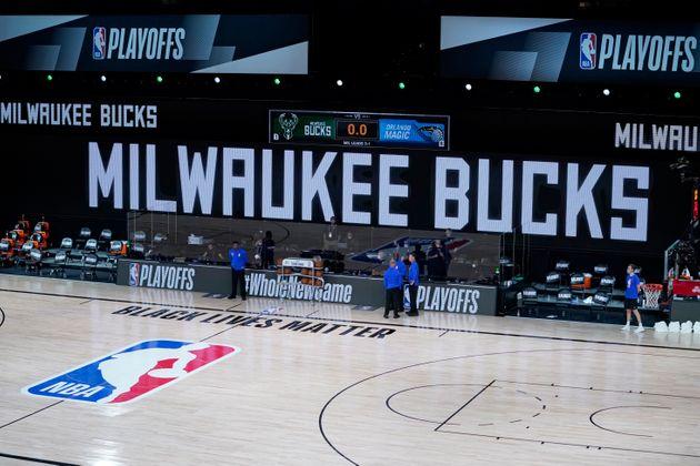 Officials stand beside an empty court at the scheduled start of an NBA basketball first round playoff...