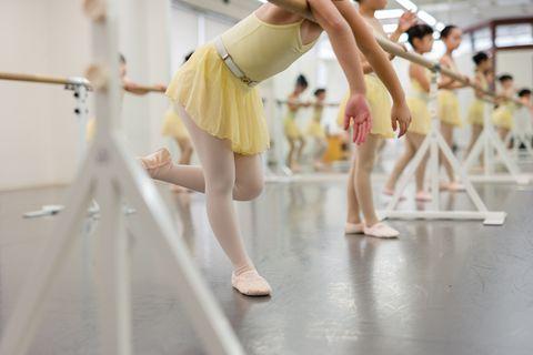 asian children of a ballet students taking recess lean on a ballet lesson bar taken at a ballet school in yokohama, kanagawa