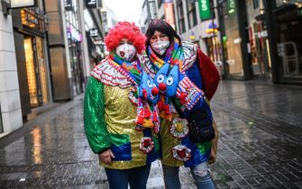 COLOGNE, GERMANY - FEBRUARY 15: A lone pair of carnival enthusiasts walk past shuttered shops in the city center on Rose Monday, the day that is normally the height of Germany's carnival season, during the second wave of the coronavirus pandemic on February 15, 2021 in Cologne, Germany. Carnival celebrations have been cancelled nationwide this year as part of ongoing lockdown measures. (Photo by Lukas Schulze/Getty Images)