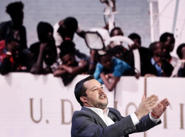 Salvini in una trasmissione televisiva: sullo sfondo i profughi della nave Diciotti