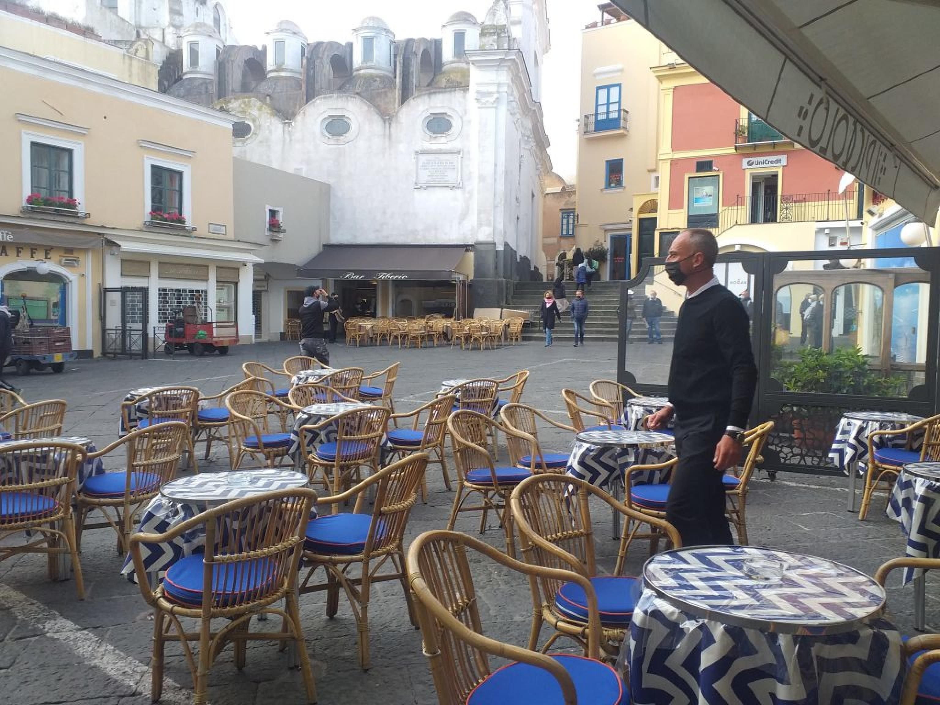 The first tables outside the bars in the Piazzetta di Capri, with the start of the yellow zone, have...