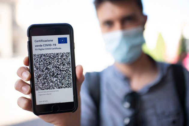 TURIN, ITALY - JUNE 30: A man shows Italy's Covid-19 Green Pass for post-vaccine travel on a smartphone...